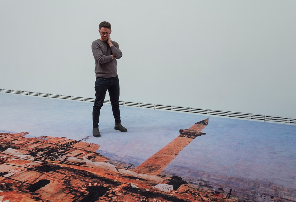 man standing on printed carpet, looking down at image