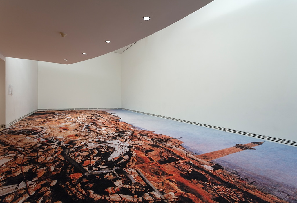 view from below, gallery, printed carpet on floor, balcony above