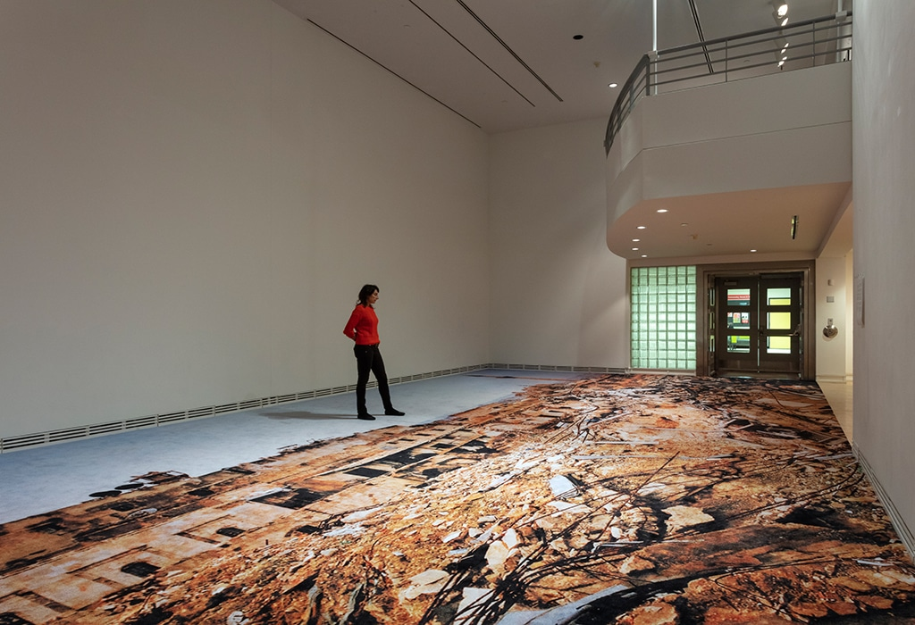 one person standing on printed carpet, view from corner of gallery