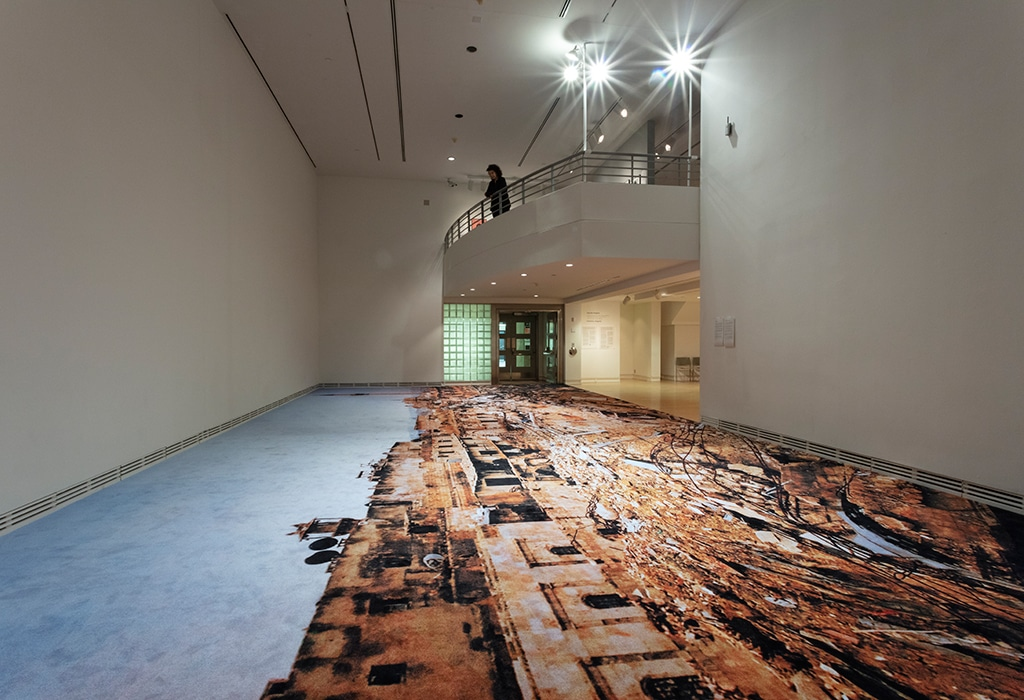 view of printed carpet on gallery floor, person looking down from balcony above